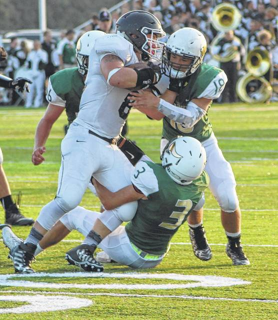 Free Canales (3), Brian Floyd (18), and Bryce Eisel of Evergreen combine to tackle Dalton Limes of Otsego in the opener on Friday.
