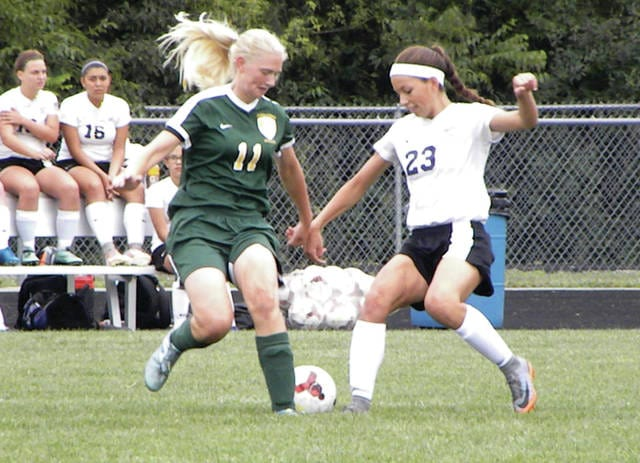 Evergreen's Sydney Kohler, left, and Haley Nelson of Swanton each go for the ball in Thursday's NWOAL girls soccer opener. The Bulldogs dominated the Vikings, 9-0.