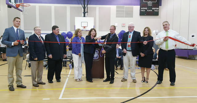 The ribbon is cut by Swanton Board of Education member Shannon Crow and superintendent Christopher Lake during a ceremony last Tuesday celebrating newly expanded district buildings.