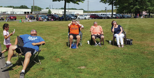 People set up near the Swanton Public Library to watch the solar eclipse. The library passed out eclipse glasses for safe viewing.