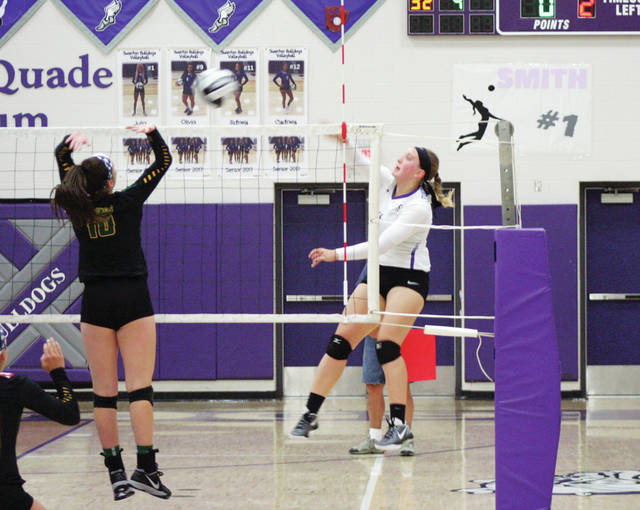 Swanton's Sidney Taylor, right, with a shot from the left side that gets blocked by Evergreen's Bailie Sutter during Tuesday's match. However, the Bulldogs went on to sweep the Vikings 25-13, 25-18, 25-23.