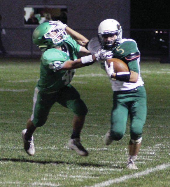 Evergreen's Hunter Van Wert stiff arms Darren Dunning of Delta as he races down field.