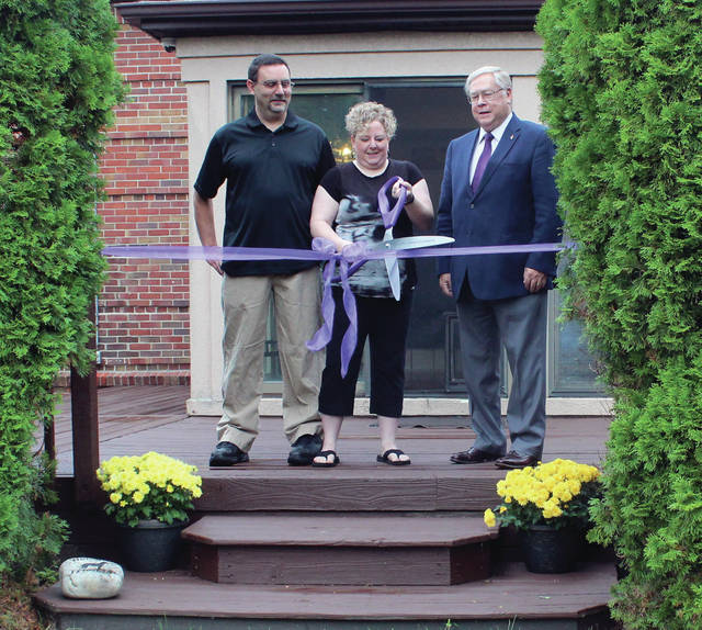 Julia Benfield cuts the ribbon at Benfield Wines in Swanton as Rob Benfield, left, and Neil Toeppe, Swanton Chamber of Commerce executive director, look on.
