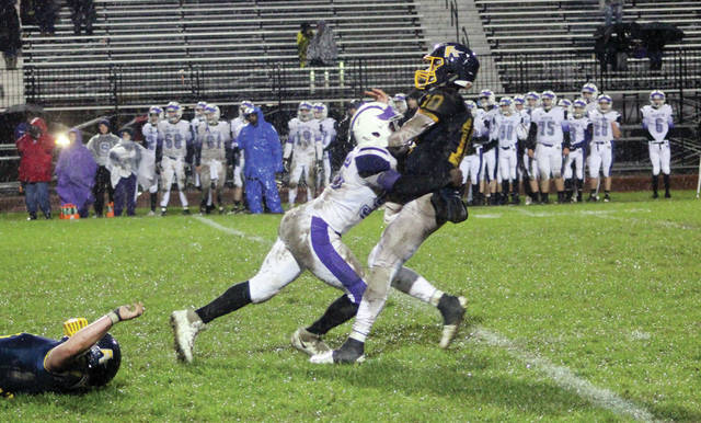 Xavier Williams of Swanton puts a hit on Archbold quarterback Gabe Petersen soon after he released the ball Friday night. The Bulldogs showed much grit in earning a 33-27 win in four overtimes.