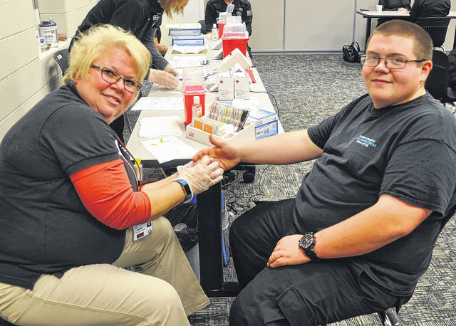 Four County Career Center seniors recently took part in a free cholesterol screening offered by the Corporate and Community Health Promotion Team of the Fulton County Health Center (FCHC) in Wauseon. High blood cholesterol is one of the four major risk factors for heart attack. This screen is made possible through money raised from the yearly Fulton County Heart Radiothon. Shown with FCHC cholesterol screener Beth Ann Beck, left, taking part in the cholesterol screening is Noah Malone (Evergreen) Law Enforcement & Security Tactics.
