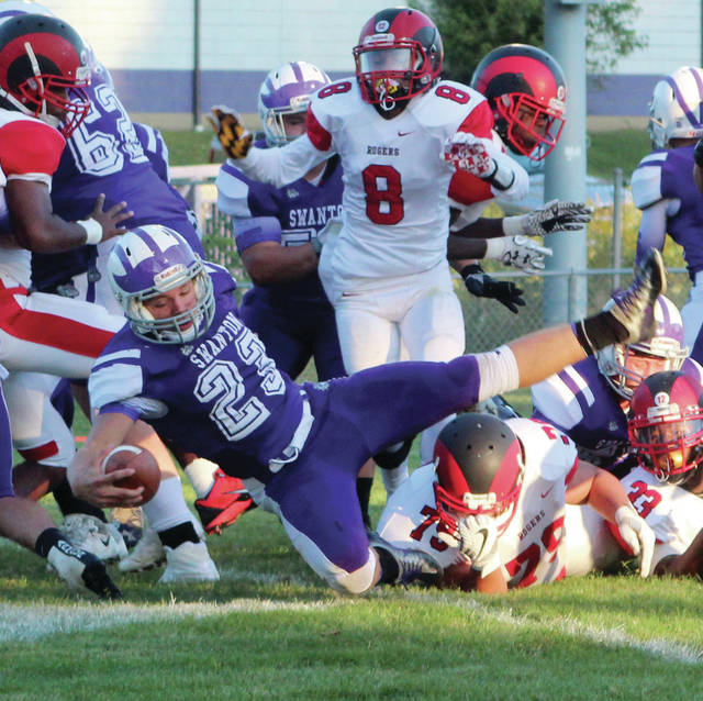 Swanton's Michael Lawniczak dives for a touchdown against Toledo Rogers earlier in the season. He was first team All-NWOAL offense for the Bulldogs.