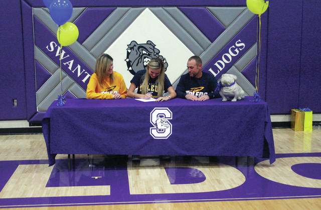 On Wednesday Julia Smith of Swanton, center, with mother Lisa Blevins and stepfather Pat Blevins by her side, signs a National Letter of Intent to continue her education and track and field career at the University of Toledo.