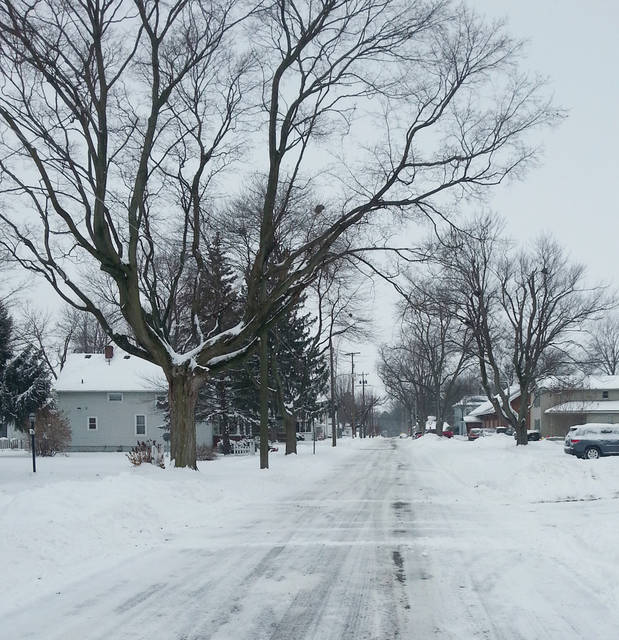Driving on snow-covered roads such as E. St. Clair Street, above, requires extra patience.
