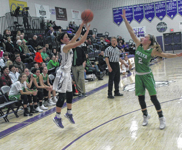 Haley Nelson of Swanton hits a three-pointer with a hand in her face from Delta's Abby Freeman during Friday's game. The Bulldogs dropped to 0-1 in the NWOAL with a 43-41 loss to the Panthers.