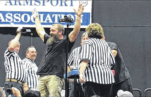Joel Hudik celebrates after winning the 198-pound title, right and left hand, at a national arm wrestling tournament in Battle Creek, Mich. last July.