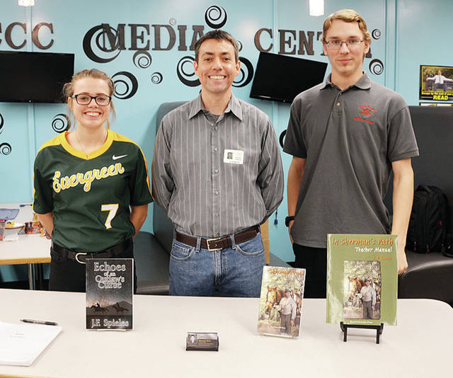 "Four County Career Center in Archbold was thrilled to have author J.F. Spieles visit students who are part of the group Page Benders, as they met to discuss his book ""Echoes of an Outlaw's Curse."" Spieles is a Wauseon native and teaches in Englewood, Ohio. Shown above during the book signing are, from left, Mackenzie Siewert of Evergreen, Spieles, and Andrew Louy of Evergreen of Evergreen. Page Benders is a group of students who meet monthly and discuss books they are reading, which are supplied free to FCCC students by the Literacy Committee."