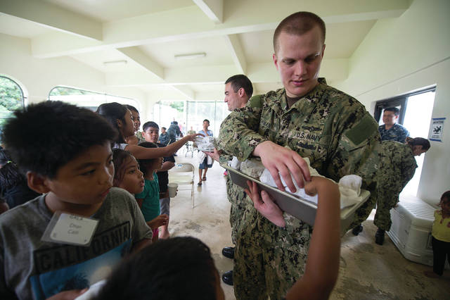 Cryptologic Technician (Collection) 1st Class Adam Wehman, from Swanton, passes lunch out to children during a community outreach event at the Guam Alternative Lifestyle Association summer camp during a regularly scheduled port visit to Agat, Guam on June 5.