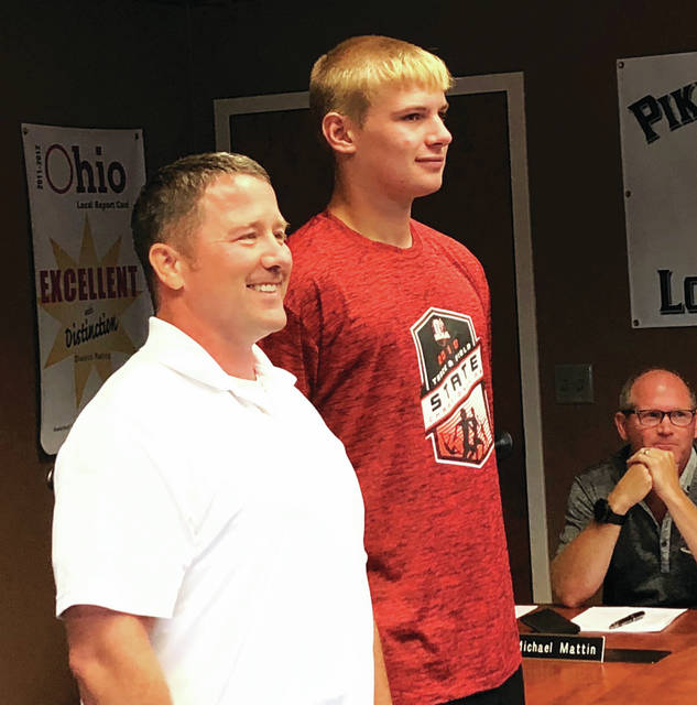 Hunter Tresnan-Reighard stands alongside Board President Mike Ford at last week's P-D-Y board meeting in recognition of his track-and-field accomplishments.
